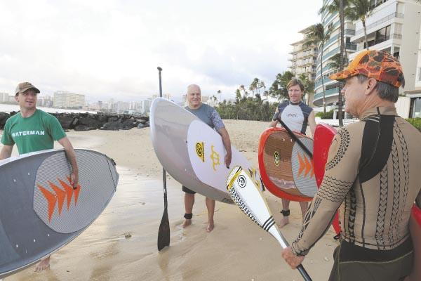 Todd Bradley, right, co-founder and CEO of C4 Waterman, meets on Waikiki Beach with his North American marketing representatives, from left, Todd Lawson from British Columbia, Steve Rogerson from Pennsylvania and Scott Sullivan from North Carolina.