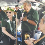 Wearing one of her familiar hats, University of Hawaii Manoa Chancellor Virginia Hinshaw plays a pakini bass at a tailgate party before the UC Davis football game on Sept. 24. UH alumnus George Hiu is to her immediate left and her husband, Bill, is in the background. Hinshaw sat down with PBN to talk story about her career plans after she leaves the chancellor position next summer. See her story on Page 8.