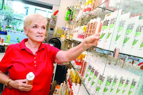 Valerie Lamoureux stocks her shelves at her Waikiki Aloe shop on Kalakaua Avenue. She, like other Waikiki merchants, expects lower sales next week as Asia-Pacific Economic Cooperation delegates arrive for meetings.