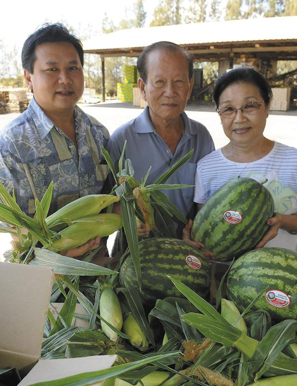 Checking out some of the company's produce are Aloun Farms General Manager Alec Sou, left, and his parents, Aloun and Somphone Sou, who founded the West Oahu business almost 20 years ago.