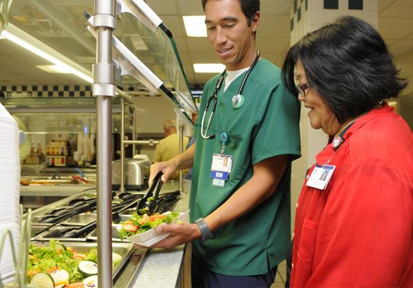 """Chris Len, a registered nurse, and Ruby Hayasaka, a registered dietician and director of nutritional services, check out some of the healthier options at the salad bar in The Bistro cafeteria at Castle Medical Center. """"One of the things that Castle does is, it makes being healthy feel like it's the 'in thing',"""" Hayasaka says."""