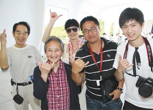 Galaxy Tour coordinator Aaron Zhang (striped shirt) escorts Chinese visitors to Pearl Harbor. From left are Lin Liyin, Li Siting and Qin Lizhe.