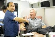 Roger Wall, vice chairman of the Sullivan Family of Cos., recently gave blood for the 89th time. He is shown sitting in a 34-foot-long bus donated by the Maurice Sullivan Family and Foodland Super Market. Mark Arakawa, nursing services specialist with Blood Bank of Hawaii, is doing the prep work for Wall's donation.