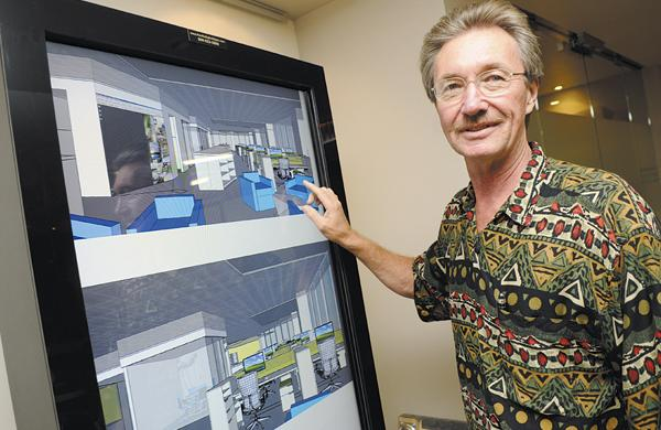 Architects Hawaii President and CEO William Brizee examines plans for the firm's new offices in the Pacific Guardian Center's Makai Tower.