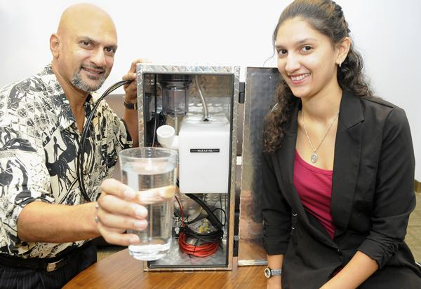Michael Maharaj, CEO of GHT Pacific, and his daughter, Shivana, the company's COO, demonstrate their product that uses hydrogen from water to help power internal combustion engines. Maharaj said he hopes to generate $1 million in sales within the next year and eventually build a manufacturing plant on Oahu.