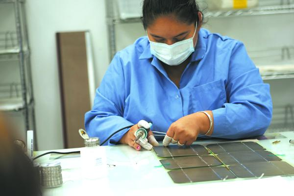 GreenPath Technologies already makes portable solar panels that fit in backpacks and are used by the military to power electronics. Part of that manufacturing process is shown here.
