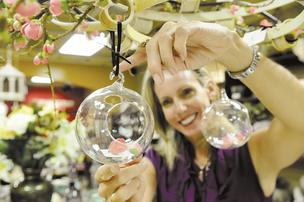 Magnolia owner Maggie Parks hangs a blown-glass bubble in her Kahala Mall shop.  She says walk-by traffic is the major source of business for her store, which is filled with items that she bought on shopping trips to Europe.