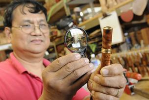 Martin & MacArthur master wood turner Mel Pascual examines a perfume atomizer made of koa, which will retail for $69. It's part of the company's less-expensive product line.