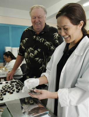 Lei Arakaki bags chocolates for the River of Life Mission's Chocolate on a Mission program as Executive Director Bob Marchant looks on.
