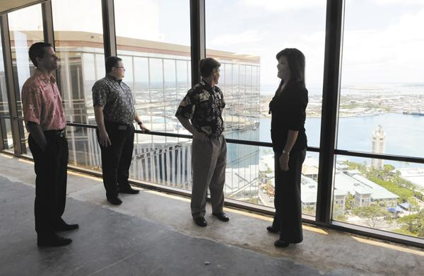 Certified Hawaii executives check out the view of Aloha Tower from the penthouse of the Pacific Guardian Center's mauka tower. The company plans to move its headquarters from Koapaka Street to the 31st-floor space. From left, Certified Hawaii CEO Jon McKenna; James Brese, Certified Hawaii controller; Jamie Brown of Hawaii Commercial Real Estate; and Stacey Tokairin, Certified Hawaii's chief operating officer.