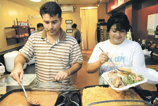 Andre and Diana Dortrait prepare plate lunches featuring their Peruvian chicken at their Horeo's Chicken restaurant at 1111 Bishop St. Their eatery has become so popular since they opened in July that they plan to add a second location, in the Chinatown Market Place, in October.