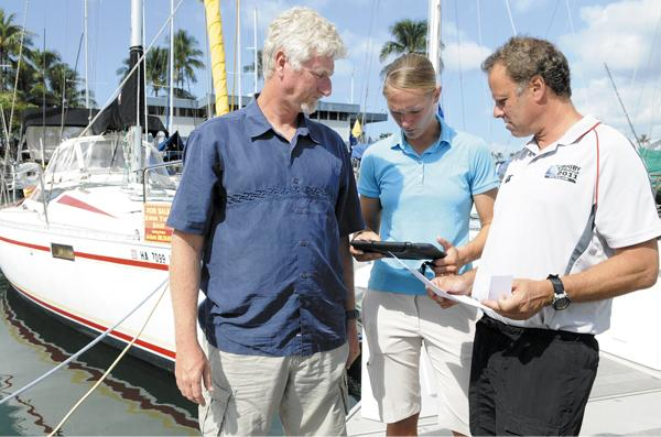 Brad Vessels, left, new owner of Kokua Yacht Sales, and his wife, Kaki, look up information on a sailboat that Rich Stone is interested in at the Ala Wai Small Boat Harbor. The Vessels are recently retired Army officers.