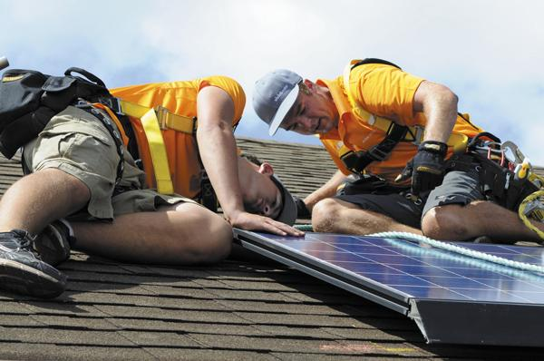 Technicians for Vivint install PV panels on a home in Waipahu earlier this year. In 2013, lawmakers will debate tax credits for future solar projects.