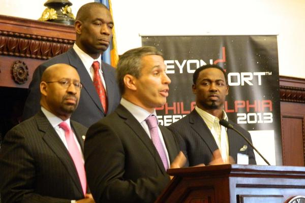 Beyond Sport Founder Nick Keller discusses his organization's upcoming summit in Philadelphia at a City Hall press conference in April as Mayor Michael Nutter, left, former Sixer Dikembe Muombo, back, and former Eagle Brian Dawkins listen.