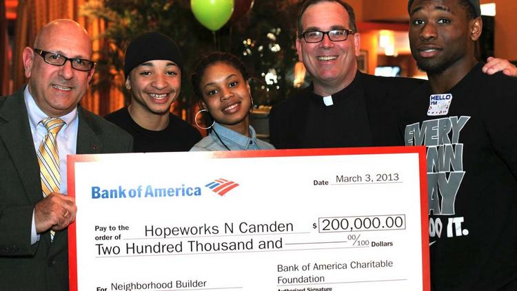 Bob Caprice presents Bank of America's $200,000 check to Father Jeff Putthoff and participants in Hopeworks at the youth organization's Roll for Hope fundraising event at Pinsetter Bar & Bowl  in Pennsauken, N.J. recently.
