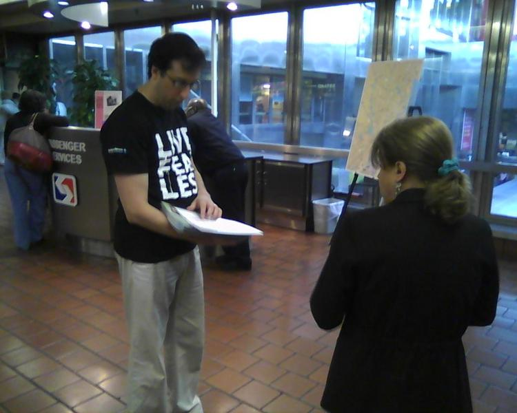 An IBC staffer hands out a free calendar, with information on the new health insurance exchanges, at Market East Station Tuesday morning.