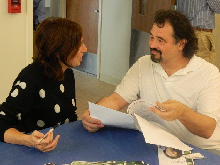 Kate Kozeniewski, a navigator with Resources for Human Development, helps Roderick Schichtel understand the new health insurance exchanges.