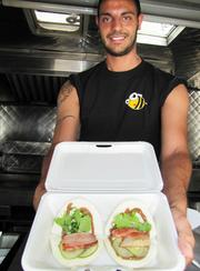 "Tyson Bees Food Truck (33rd and Spruce) specializes in Korean cuisine. One of the Yelp reviews said of the truck's pork bun, ""The bun was a soft pillow for the decadent pork."" Indeed, ours arrived with the pillowy bun, topped with smoked pork belly, slices of cucumber, parsley and a spicy sauce. Here a worker named Sal holds it up for inspection."