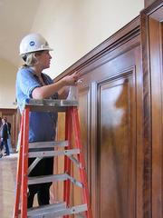 A conservation technician works on wood paneling inside the Rodin Museum.