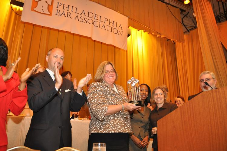 Stephanie Resnick accepts the Philadelphia Bar Association's Sandra Day O'Connor Award on June 28 at the Hyatt at The Bellevue. At left is Chancellor Scott F. Cooper and to the right are Women in the Profession Committee Co-Chairs Nikki Johnson-Huston and Kimberly Ruch-Alegant.
