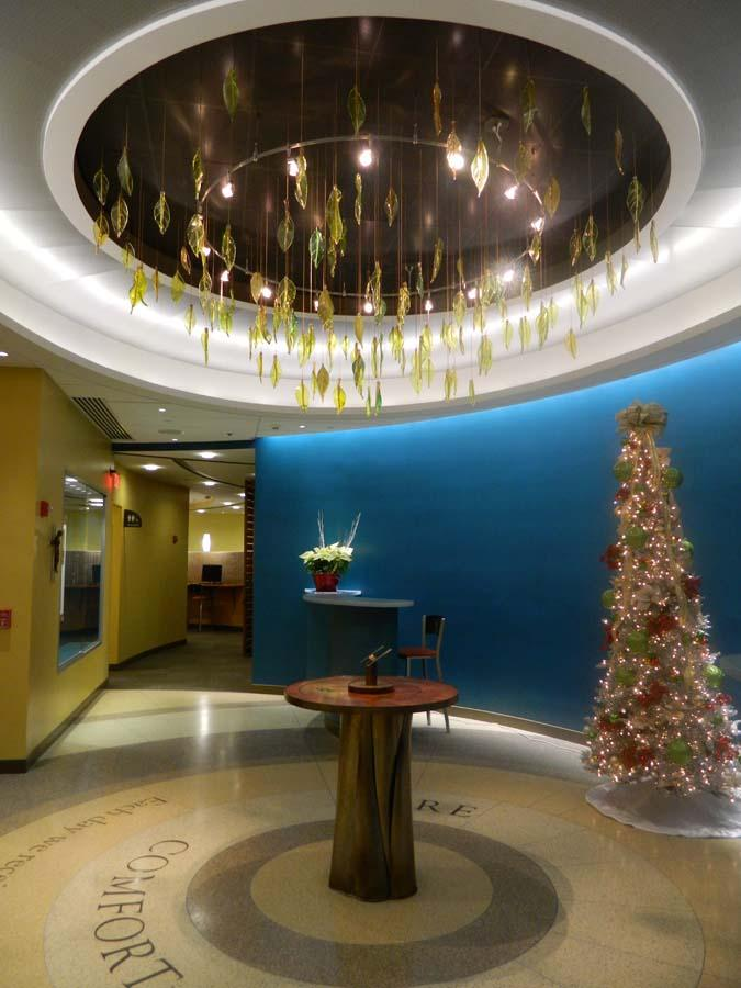 The front lobby area at Holy Redeemer HealthCare at Bensalem — where features include a tree stump pedestal and hand-blown leaves hanging from the ceiling — sets the tone for the medical office's nature theme.