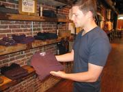 Brian Linton, the 26-year-old founder of United By Blue, shows a Henley-style shirt to be sold in the store.