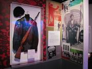An area devoted to the Black Panther Party shows the militant group's uniform of leather jacket, beret and shotgun. At right, is the famous portrait of Panther leader Huey P. Newton.