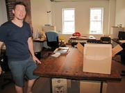 Founder Brian Linton with work tables that were salvaged from a shuttered high school's shop class.