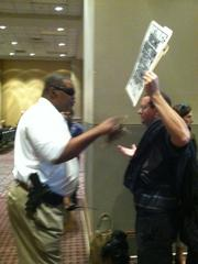 A police officer urges a protester to leave the casino hearing.