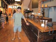 Mike Cangi of United By Blue shows off the cafe bar, which was assembled from wood reclaimed from the old Samuel Machinery Co. elsewhere in Old City and a church at 10th and Callowhill. The counter itself was made from old floor joists, sanded and finished.
