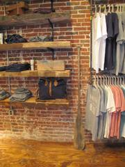 The store features exposed brick walls, wood floors, shelves made of reclaimed wood, old artifacts and so on.