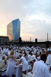 A crowd shot of Diner en Blanc, a spontaneous dinner party held on the JFK Bridge (with 30th Street Station and the Cira Centre in the background).