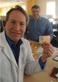 X-Card Holdings founder and President Mark Cox holds the insert layer of a new technologically advanced plastic card while David Ludin looks on.