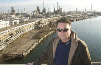 Jim Savage, president of U.S. Steelworkers Local 10-1, with the Sunoco refinery in the background. Savage expects the Port of Philadelphia to benefit.