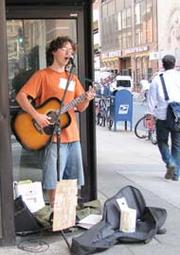 A busker plays for tips in the doorway of the former Fleet Bank on the southeast corner of 15th and Walnut streets.