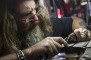 Taking a break from the open road, Ganem works on a piece of NightRider jewelry.