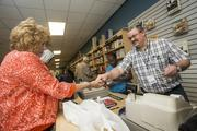Book Warehouse manager Billy Reese hands over some change to Glendale resident Nancy Jordan. Book Warehouse is one of around 80 stores that opened at Tanger Outlets at Westgate Nov. 15.