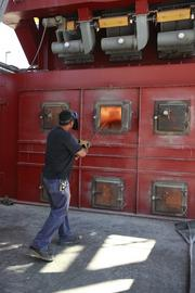 A worker stokes the fires of a biomass boiler at the Frito-Lay facility in Casa Grande. The power plant replaces about 80 percent of the natural gas used by the company in making chips.
