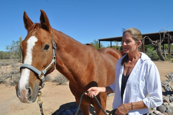 Mary Hadsell, executive director of Camelot Therapeutic Horsemanship, with Cliffy, one of Camelot's eight therapeutic horses at its facility in North Scottsdale.