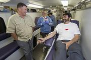Chandler Police Department Commander Matt Christensen, left, visits with Latif Ahmed, president of the Ahmadiyya Muslim community as Ahmed donates blood in a United Blood Services bus. Also pictured is Lisa Hidaro with UBS.