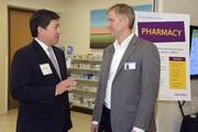 Edward Kim, president and CEO of Cigna Medical Group, left, speaks with Pharmacist Eric Luecht at CMG's grand opening of its downtown clinic and urgent care center.