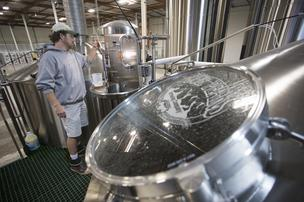 Neal Huttenow, a brewer at Four Peaks Brewing Co. in Tempe, checks a batch being prepared at the company's new location.