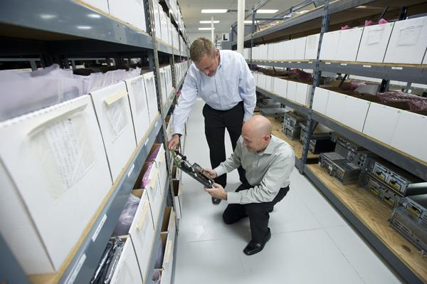 Charles Layne, left, and Aaron Zeper check inventory in the parts warehouse at Signature Technology Group in Phoenix. The company specializes in keeping older business computers up and running.