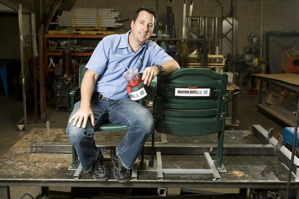 Shad Bruce, founder of Branded Seats, shows off some of the snap-on advertising his company has developed for arena and stadium seating.