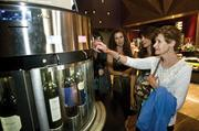 Moviegoer Nancy Mongan scans the wine selection at the iPic Theaters, which opened recently at the Scottsdale Quarter. More Valley theaters are adding amenities such as upscale food and spirits to their offerings.