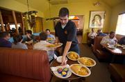 Waiter Patrick Daims serves customers at Ajo Al's near 16th Street and Camelback Road in Phoenix. When one of the restaurant's workers is sick, they usually call one another to arrange shift coverage.