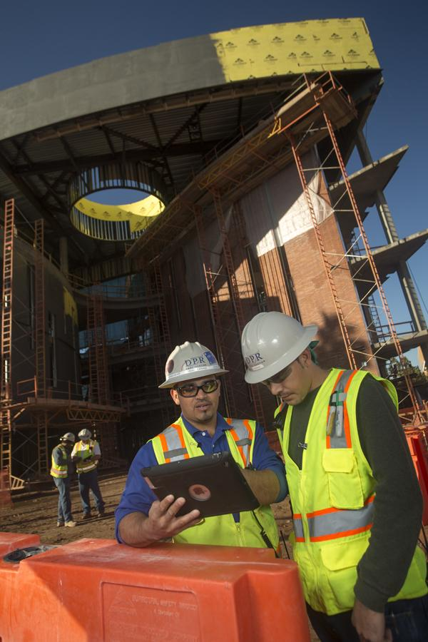 Construction workers Ricardo Erives, left, and Jonatan Heras both use iPads in their day to day functions on the job site of the W.P. Carey School of Business In Tempe.