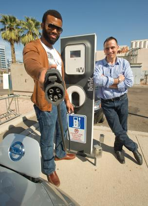 David Ovienmhada shows the plug he uses at the charging station behind Monti's La Casa Vieja in Tempe, owned by Michael Monti, right. Ovienmhada owns a Nissan Leaf.