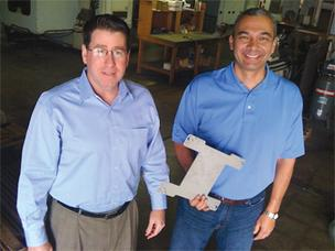 Pivot Manufacturing Inc. co-founders Jack Cuddihy, left, and Steve Macias show a metal tray the company custom-made to hold a computerized component for a defense project.