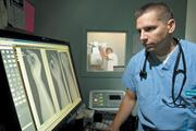 NextCare Urgent Care certified physician's assistant David Hermann reviews a patient's X-rays.